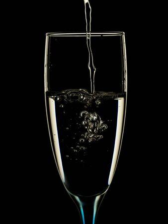 Elegantes Bild in Gläsern wird mit sauberem Wasser auf schwarzem Hintergrund gegossen