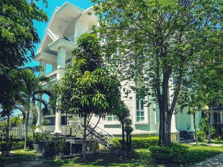 One beautiful three-story house with palm trees, trees, and landscape design in the summer. An Vien. Nha trang. Vietna.