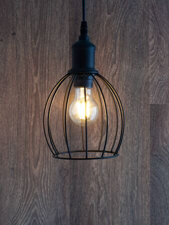 decorative chandelier on a background of a wooden wall. Chandelier Lighting. The lamp with LED lamps. Stock Photo