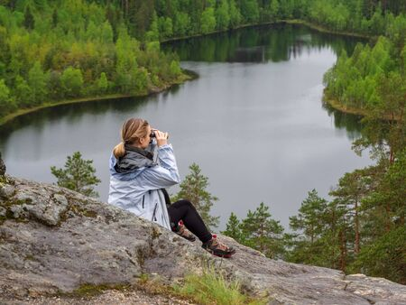 woman looks through binoculars. tourist girl on a rock in a forest near a lake