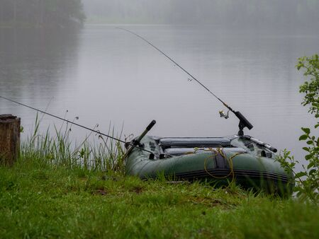 Inflatable boat with fishing rods on the lake