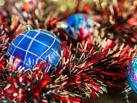 Christmas balls on a background of lights and bright beautiful tinsel. Christmas design card with place for text. Xmas decorations. Good New Year spirit.