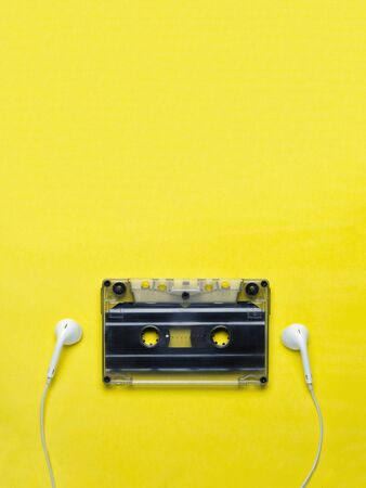 Headphones and old audio cassette on yellow background/