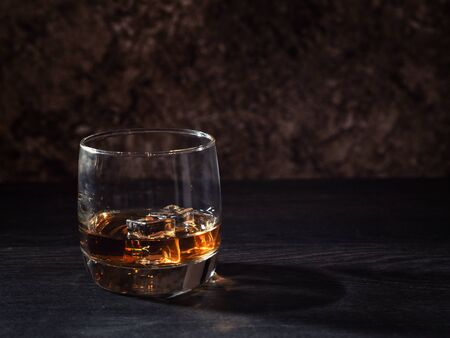 Whiskey splash in a glass with ice on a wooden table.