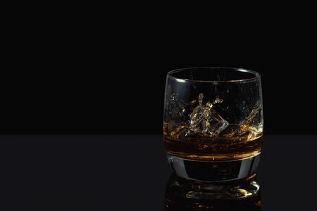 Whiskey splash in glass with ice on a dark background.