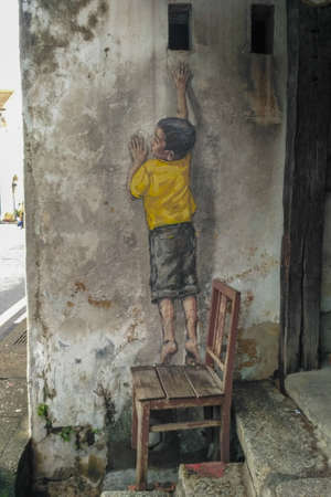 PENANG, MALAYSIA-2018-01-05: Street Mural entitled 'Reaching Up' painted by Ernest Zacharevic in Penang on July 6, 2013. It was painted in conjunction with the 2012 George Town Festival