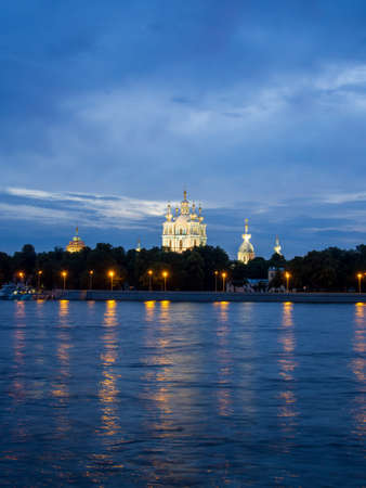 View of the Smolny Cathedral from the Neva at night on a cloudy summer day. Russia, Saint-Petersburg