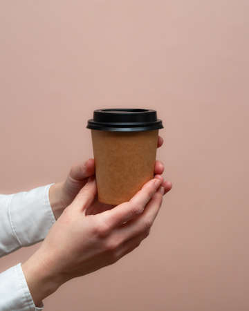 Woman hands hold paper cup on pink background. Copy space.