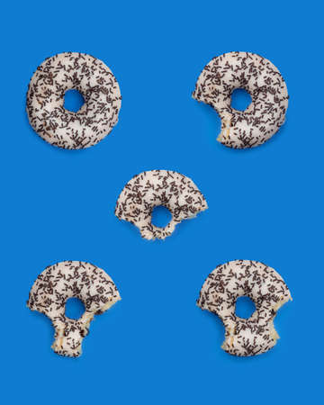 Donuts with icing on a pastel blue background. Sweet donuts. Фото со стока