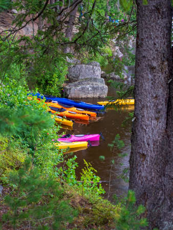 Photo of Colorful kayaks by river Фото со стока