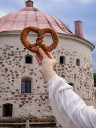 Vyborg pretzel in hand against the background of the old round tower (Symbol of Vyborg) Фото со стока