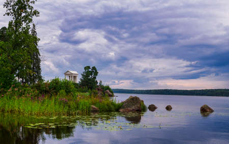 Mon Repos Park in Vyborg, Russia.View of the island and the trees reflected in the water.View of the boat dock and the white gazebo with a colonnade in the distance.