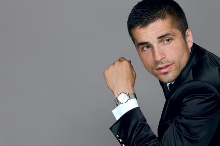 beau jeune homme porte une montre dans un costume d'affaires