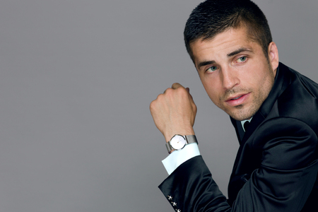 handsome young man wears a watch in a business suit