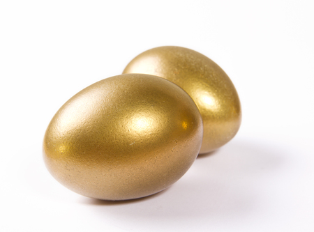 priceless: Two gilt Easter eggs lying on a white background
