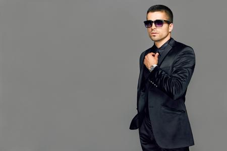 poses de modelos: Hombre apuesto joven elegante con gafas y observadores. Retrato de moda Studio.