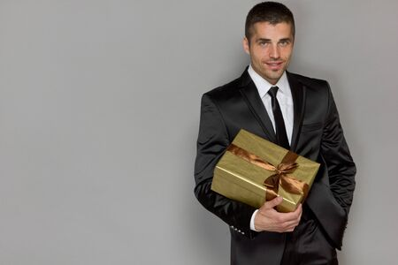 red gift box: handsome young man with a gift of gold is on a gray background studio Stock Photo