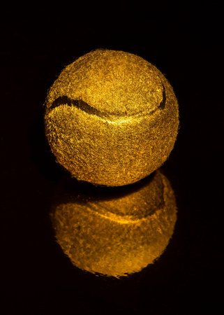 fuzz: Festive golden tennis ball on black background big shot Stock Photo