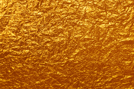 gold colour: crumpled golden foil glossy holiday horizontal background