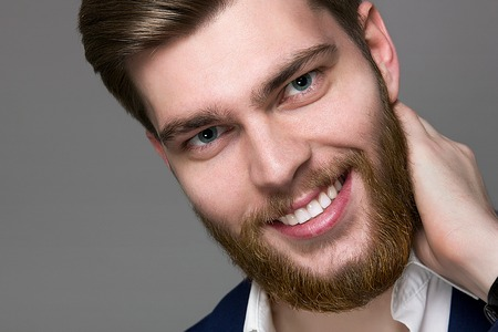 blond hair: portrait of a young man with a big beard in the studio on a gray background Stock Photo