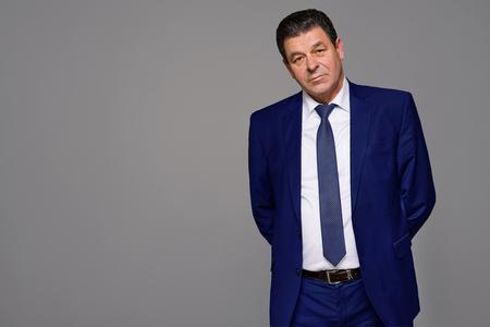 mature business man: an elderly man model on a gray background, studio