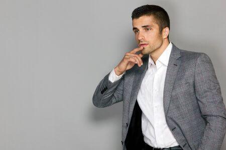 modelo masculino con una chaqueta gris mira cuidadosamente