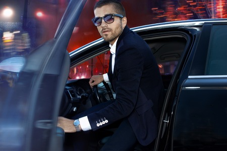 Handsome brutal man in luxury car. Night life.