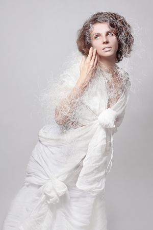 Kunstfoto eines Mädchens in einem Haute-Couture-Kostüm eines schicken weißen Baumwollkleides auf weißem Hintergrund in Isolation