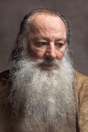 Anciano con una larga barba con tristeza sobre un fondo gris