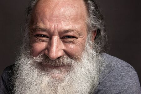 a gray-haired old man of sixty, seventy, with long gray hair and a big white beard smiling widely