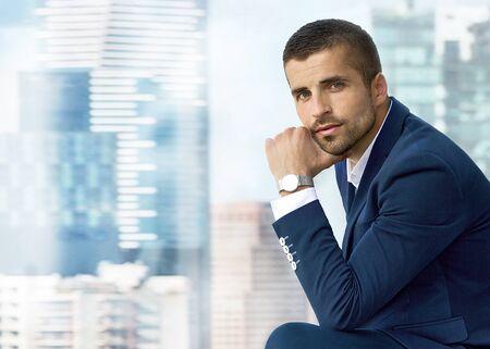 Mann in blauem Anzug und teurer Uhr posiert vor dem Fenster