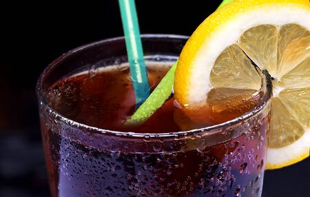 Drink carbonated in a glass with straws and lemon on a brown background Standard-Bild - 128778912