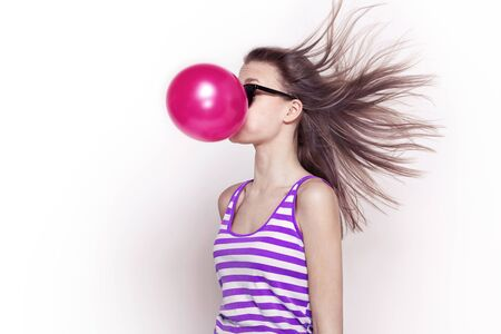 girl with flying hair inflates a pink balloon, humor Banco de Imagens