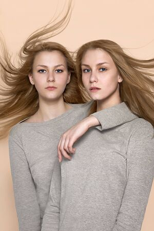 Two twin girls in a gray sweater posing in the studio on caramel pastel background