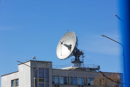 Dish antenna for satellite communications on the roof of an office building Stock Photo