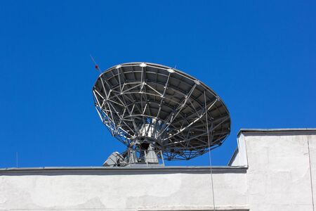 Metal reflector dish in action on the roof of an office building