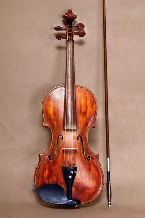 Orquesta de instrumentos musicales de violín cerca aislado sobre fondo marrón antiguo