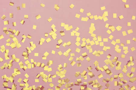 Pink festive background with golden sparkles in the shape of squares.