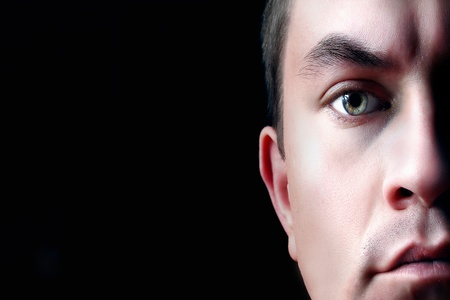 A dramatic portrait of a young man, isolated on black background. Half face photo