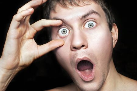 Portrait of a frightened or surprised guy close up. Isolated on a black background Stock Photo - 8790604