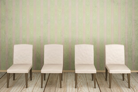 An empty room with dirty striped wallpaper and four chairs Stock Photo
