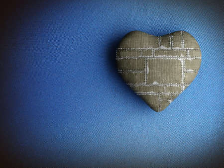 Patched heart on a dirty blue fabric background