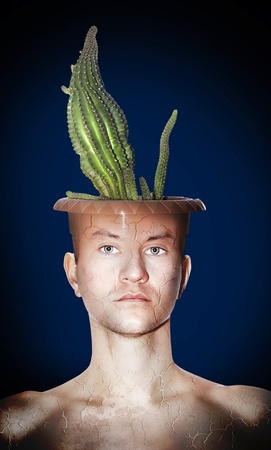 Portrait of young man with a pot on her head, which is growing cactus. The body is cracked. Background - projectors are not in focus.