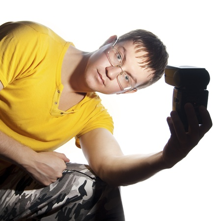 Guy with glasses and yellow shirt. Illuminates himself flash in his left hand. Isolated on a white background. Stock Photo