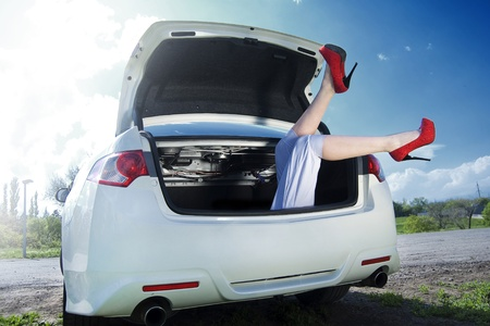 Legs girl in red shoes visible from the trunk of a white car. Against the blue sky and grass