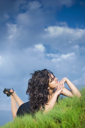 A beautiful girl relaxing on a green hill against the blue sky with clouds.