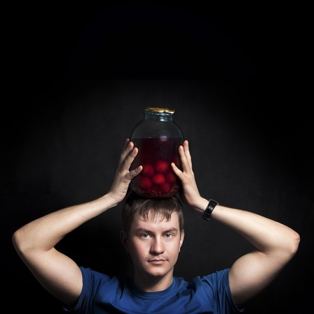 Young man with a balloon conserved plums. Isolated on a black background