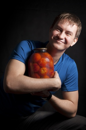Fairly young man with a balloon conserved tomatoes. Isolated on a black background