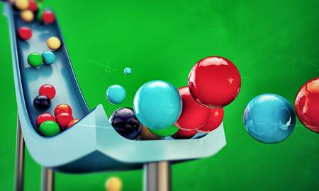 multicolored gumballs: gumballs sliding down isolated on green background Stock Photo