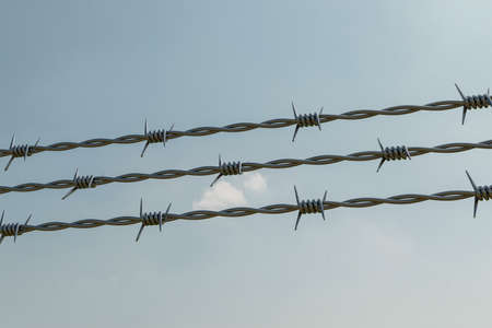 Barbed wire fence of a restricted area under blue sky 3d illustration Stock Photo